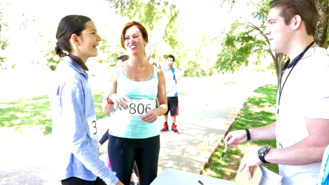 Volunteer greeting mother and daughter team as they register for marathon race