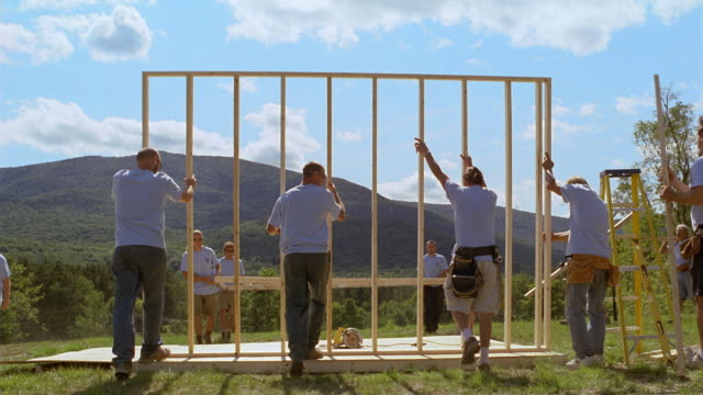 MS Volunteer homebuilders lifting wood frame and hammering it into place with green mountains in background/ Manchester, Vermont