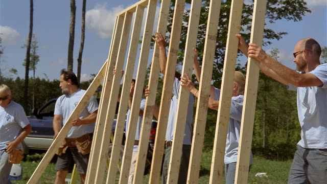 vídeos de stock, filmes e b-roll de ms volunteer homebuilders lifting wood frame and hammering it into place with green mountains in background/ manchester, vermont - 25 30 anos