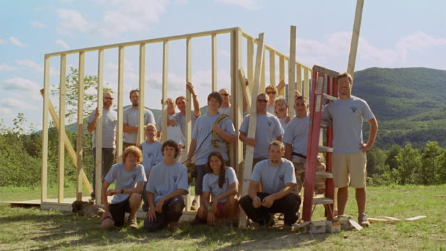 WS PORTRAIT Volunteer homebuilders posing with wooden house frame/ Manchester, Vermont