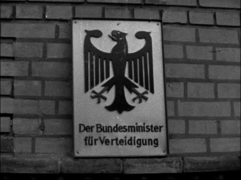 volunteer in federal army presented with book; west germany: bonn: ext federal army soldier getting out of car on arrival sign 'der bundesminister'... - 西ドイツ点の映像素材/bロール