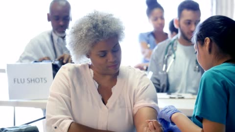 volunteer nurse prepares to give woman flu vaccine - medical clinic stock videos & royalty-free footage