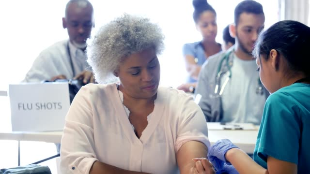 volunteer nurse prepares to give woman flu vaccine - proiezione evento pubblicitario video stock e b–roll