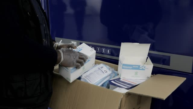 a volunteer opens boxes to take mask packs during a distribution facial masks and leaflets offered by the ile de france region to commuters at the... - delivering stock videos & royalty-free footage