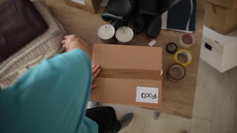volunteer packing donation boxes in charity food bank - volunteer stock videos & royalty-free footage