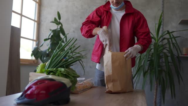 vidéos et rushes de faire ses valises volontaires dans un sac en papier pour livraison pendant la pandémie de coronavirus - sac de shopping