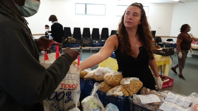volunteer provides food to a local resident at the albrighton community centre which partners with environmental charity hubbub to create the... - brian dayle coronavirus stock videos & royalty-free footage