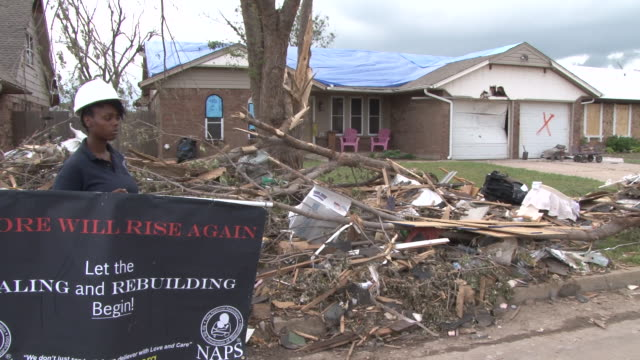 stockvideo's en b-roll-footage met a volunteer rescue worker holds up a sign of hope and recovery in front of a badly damaged home in moore ok in the wake of the devastating ef5... - 2013