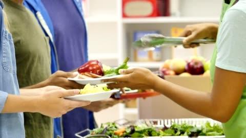 vídeos y material grabado en eventos de stock de voluntario sirve comida sana a la gente en el comedor - voluntario
