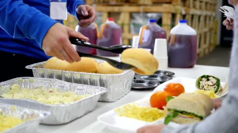 vídeos y material grabado en eventos de stock de voluntarios que sirve comida para niños en línea en cocina libre - voluntario