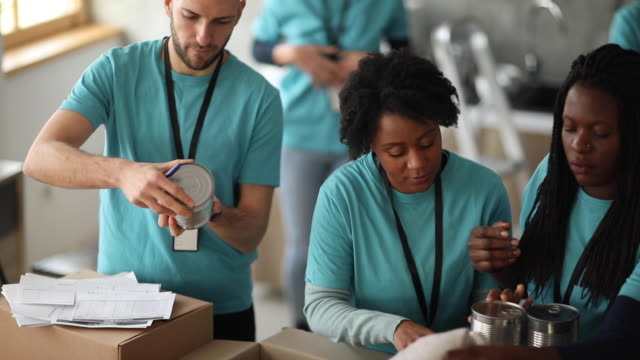 volunteer team packing donated food and other goods - altruism stock videos & royalty-free footage
