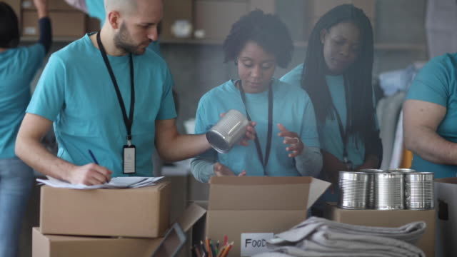 volunteer team packing donated food - t shirt stock videos & royalty-free footage