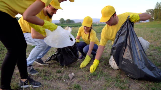 volunteer together pick up trash in the park - altruism stock videos & royalty-free footage