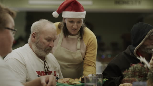 volunteer wearing santa hat serving food in homeless shelter / provo, utah, united states - homeless shelter stock videos & royalty-free footage