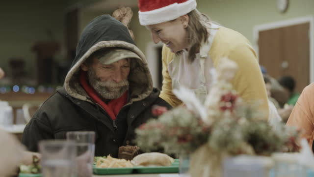 volunteer wearing santa hat serving food to smiling man in homeless shelter / provo, utah, united states - canteen stock videos & royalty-free footage