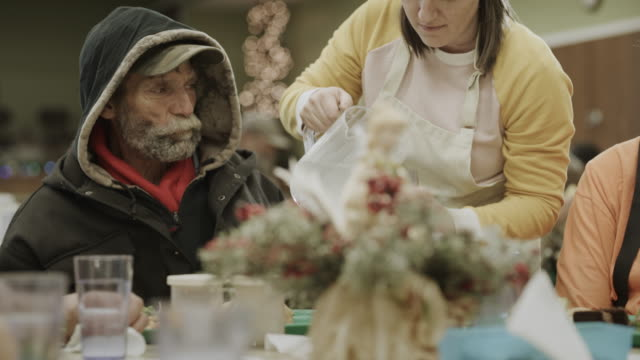 volunteer wearing santa hat serving water to man in homeless shelter / provo, utah, united states - provo stock videos & royalty-free footage