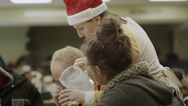 volunteer wearing santa hat serving water to woman in homeless shelter / provo, utah, united states - soup kitchen stock videos & royalty-free footage