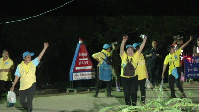Volunteer workers cheer while leaving the Tham Luang cave area after divers evacuated some of the boys among a group of 13 trapped in a flooded cave...