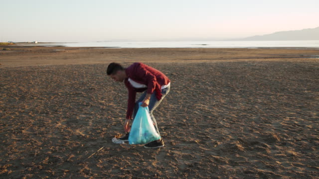 Volunteer young man picking up a bottle from the sand of a beach