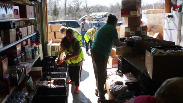 volunteers at pantry 279, located at trinity lutheran church, prepare donated food to give to families experiencing food insecurity during the... - rural scene stock videos & royalty-free footage