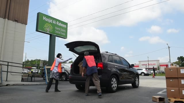 volunteers at the islamic society of central florida distribute food from the second harvest food bank to needy families on april 9 2020 in orlando... - unemployment covid stock videos & royalty-free footage