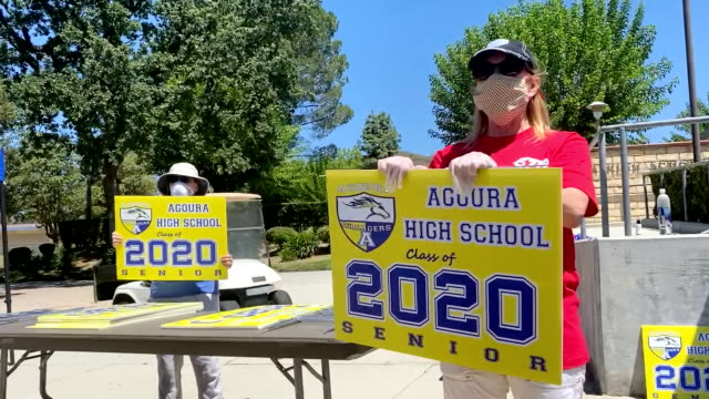 volunteers cheer on the graduating high school class of 2020 with a lively drive by. - graduation stock videos & royalty-free footage