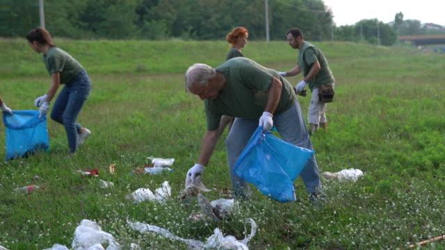 freiwillige reinigen gemeinsam die umwelt - gartenhandschuh stock-videos und b-roll-filmmaterial