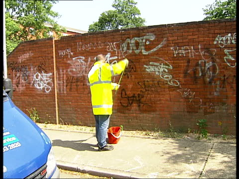 Volunteers cleaning up west London parkland and graffiti Exact location uknown Men wearing reflective yellow jackets cleaning graffiti off brick wall...