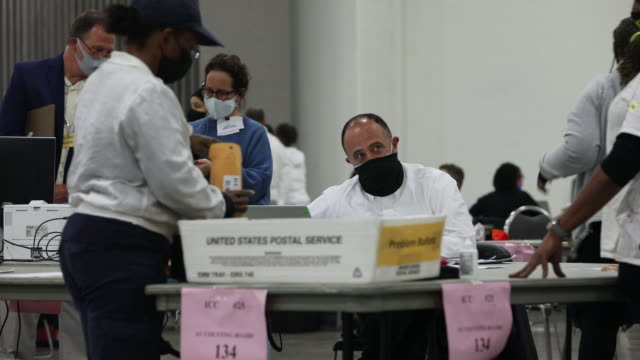 volunteers counting absentee ballots at tcf center in detroit, michigan, u.s., wednesday, november 4, 2020. - ballot slip stock videos & royalty-free footage