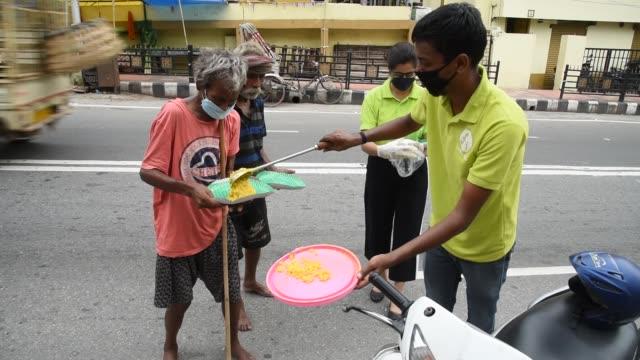 volunteers distribute food to people in need during covid-19 weekend lockdown, in guwahati, sunday, 26 july 2020. - feeding stock videos & royalty-free footage