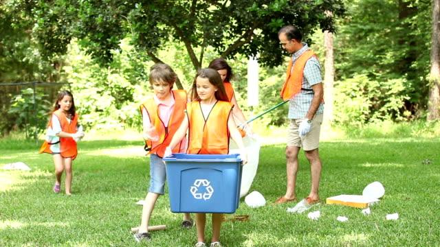 vidéos et rushes de bénévoles: famille nettoient leurs community park. poubelle de recyclage. - 8 9 ans