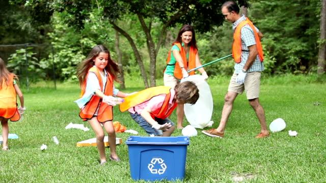 volontari: famiglia clean up loro comunità park. bidone per il riciclaggio. - 8 9 anni video stock e b–roll