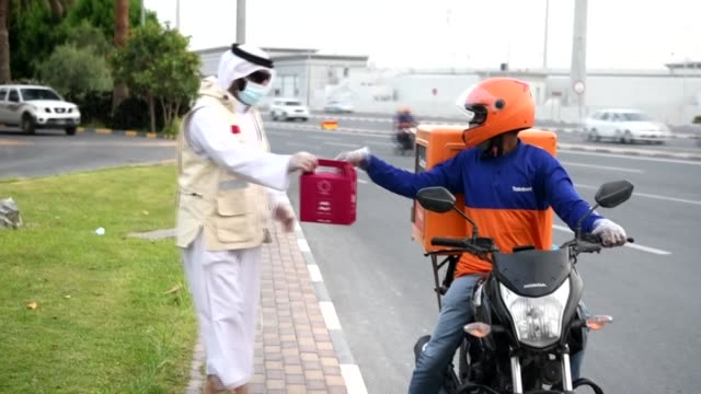 volunteers from the ngo qatar charity distribute meals for iftar, when muslims break their ramadan fasts, to employees and migrant workers on one of... - qatar stock videos & royalty-free footage