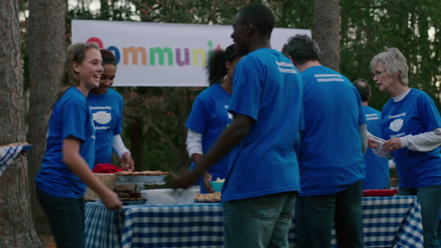 stockvideo's en b-roll-footage met volunteers gather for community picnic - schenking