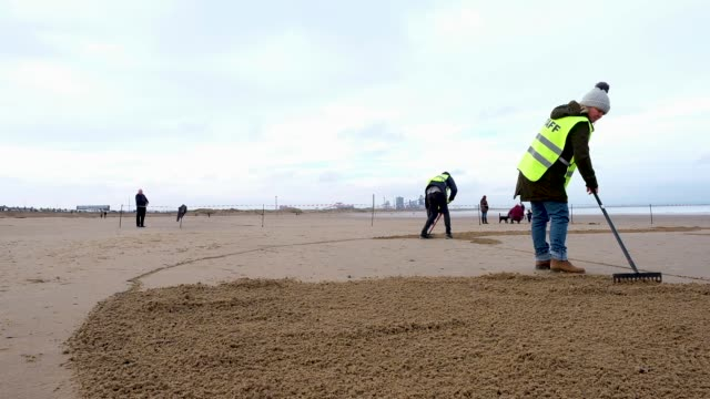 volunteers gather on redcar beach to take part in a large scale sand portrait project called 'pages of the sea' on november 11 2018 in redcar england... - remembrance day stock videos and b-roll footage