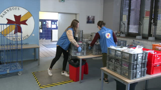 vídeos y material grabado en eventos de stock de volunteers give food to the homeless during distribution hour at one of the points of the berliner stadtmission charitable organization on april 9,... - number 9