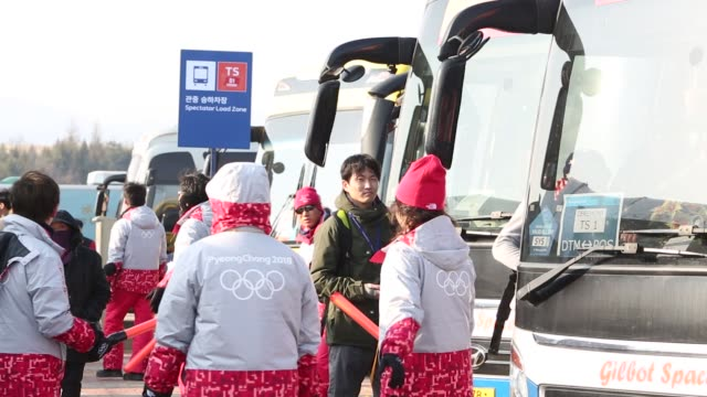 volunteers give visitors directions to shuttle buses for the olympic stadium ahead of the 2018 pyeongchang winter olympic games in the hoenggyeri... - winter sports event stock videos and b-roll footage