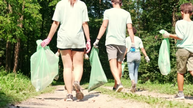 volunteers holding garbage bags walking outdoors in nature - dedication stock videos & royalty-free footage