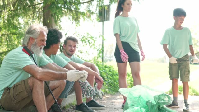 volunteers in green shirts sitting on the ground taking a break from cleaning the environment - three quarter length stock videos & royalty-free footage