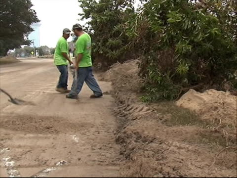 volunteers in light green shirts shoveling sand off roadway cleaning up mud debris from road in north carolina in aftermath of hurricane irene - north carolina us state stock videos & royalty-free footage