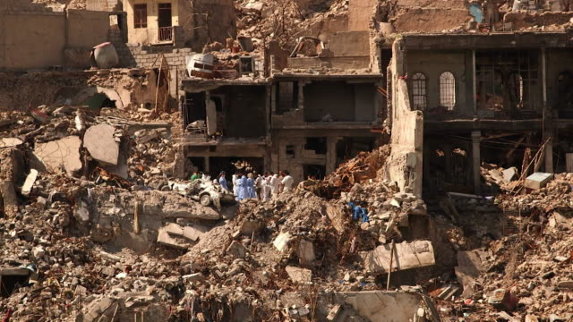 volunteers in mosul iraq removing dead bodies from houses destroyed by air strikes - cadavere video stock e b–roll