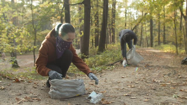 volunteers in protective face coverings cleaning nature from masks and plastic - lift stock videos & royalty-free footage