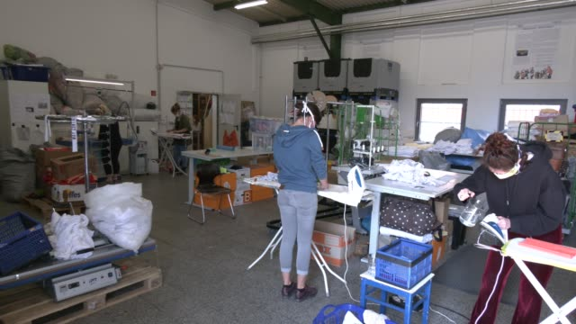 stockvideo's en b-roll-footage met volunteers iron fabric to make masks for homeless, project by the berliner stadtmission charitable organization on april 9, 2020 in berlin, germany.... - number 9