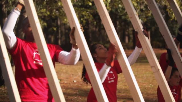volunteers lift frame together - volunteer stock videos & royalty-free footage