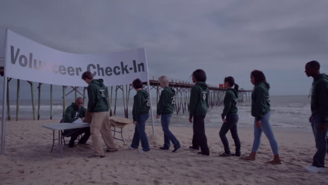 volunteers line up for check in - altruism stock videos & royalty-free footage