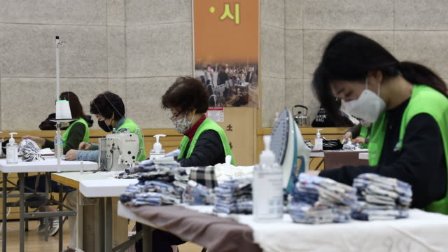 volunteers manufacture protective cotton masks using sewing machines at the nowon district government office building in seoul south korea on monday... - coreano video stock e b–roll