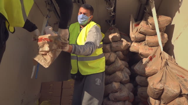 volunteers of elliniko area in athens go door to door on saturday to distribute hundreds of parcels containing food and basic necessities to people... - sharing stock videos & royalty-free footage