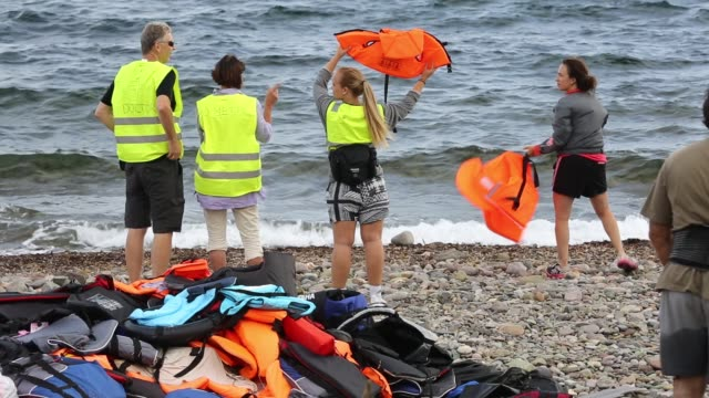 volunteers on the beach wave life jackets attract syrian migrants to their landing spot arriving from turkey on the beach on the greek island of... - isil konflikt stock-videos und b-roll-filmmaterial