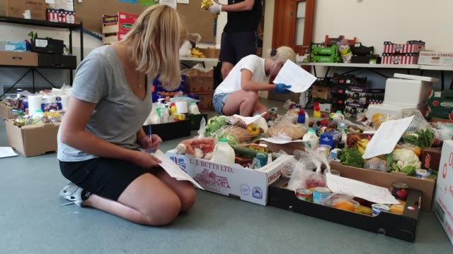 volunteers organise and pack food boxes at albrighton community centre which partners with environmental charity hubbub to create the community... - brian dayle coronavirus stock videos & royalty-free footage