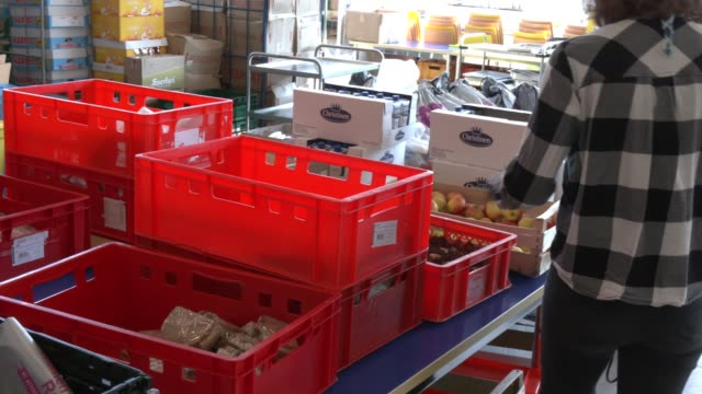 stockvideo's en b-roll-footage met volunteers pack emergency food packages for distribution to the homeless in a project by the berliner stadtmission charitable organization on april... - number 9